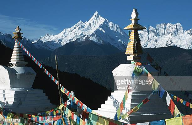 Stupas and prayer flags in front of Meili Shan a sacred mountain for Tibetan Buddhists Deqin Yunnan Province Sitting just within the borders of...
