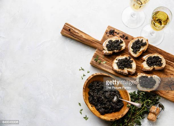 sturgeon black caviar in wooden bowl, sandwiches and champagne on white background copy space - sturgeon fish stock pictures, royalty-free photos & images