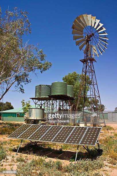 Solar panels provide electricity for desert homes and windmills water.