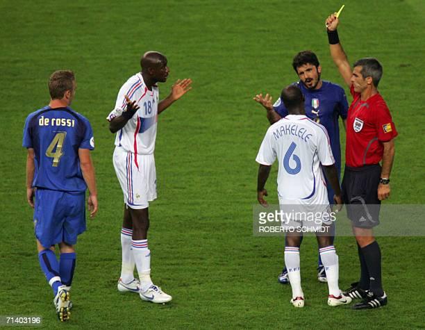 Argentine referee Horacio Elizondo shows a yellow card to French midfielder Alou Diarra as Italian midfielder Gennaro Gattuso and French midfielder...