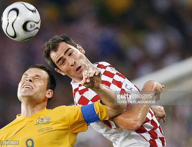 Croatian defender Igor Tudor goes for a header with Australian midfielder Josip Skoko during the World Cup 2006 group F football match Croatia vs...