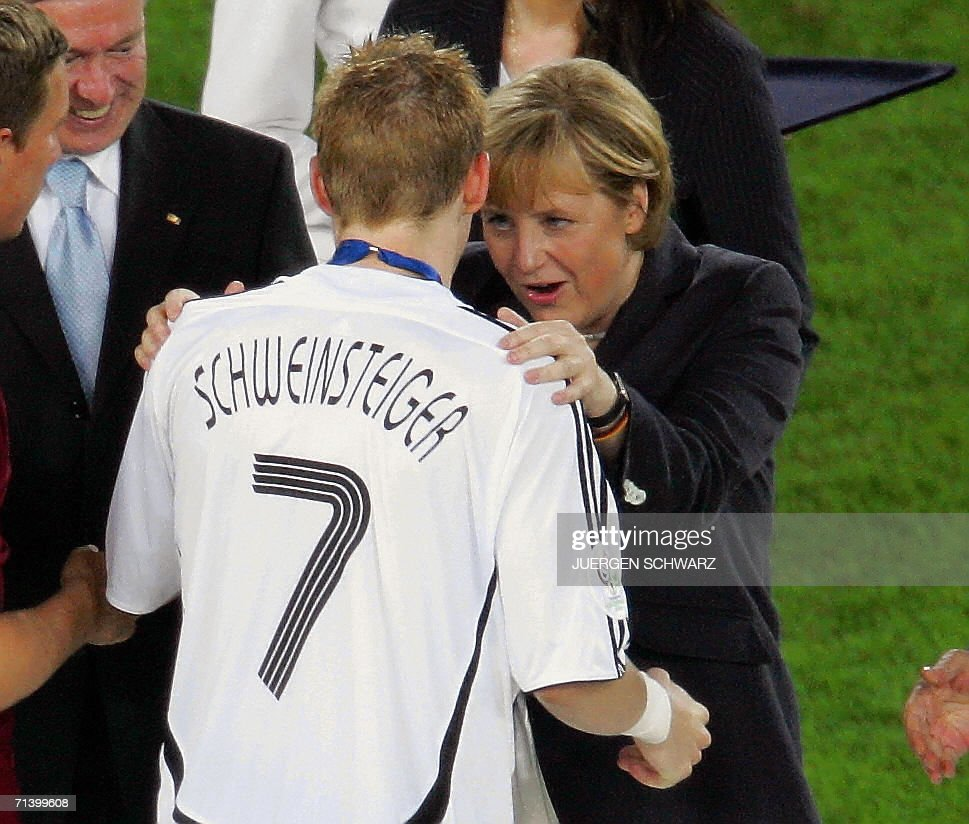 German Chancellor Angela Merkel (R) congratulates German midfielder Bastian Schweinsteiger during the third-place podium ceremony 08 July 2006 in Stuttgart, of the World Cup third-place play-off football match between Germany and Portugal. Germany won 3-1.