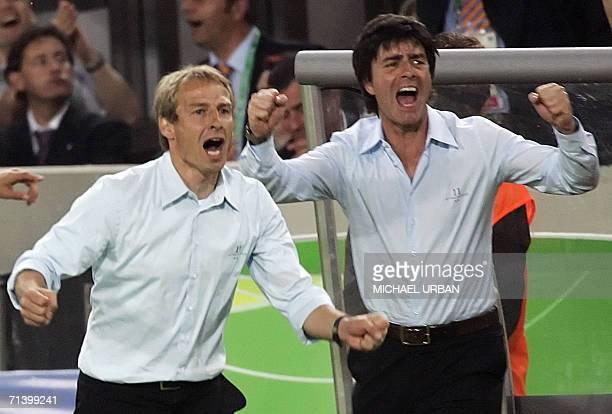 German head coach Juergen Klinsmann and German assistant coach Joachim Loew celebrates after German midfielder Bastian Schweinsteiger scored the...