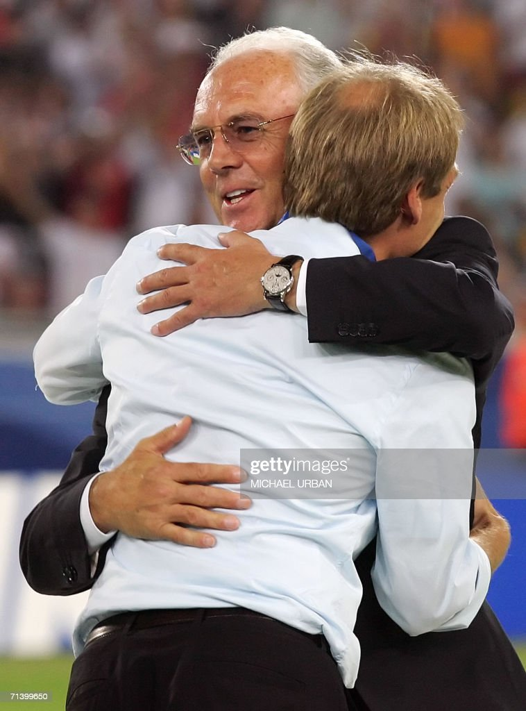 German head coach Juergen Klinsmann (L) is embraced by German football legend and president of the World Cup organising committee Franz Beckenbauer (R-facing) during the medal presentation ceremony following the team's victory in the third-place playoff 2006 World Cup football match between Germany and Portugal at Stuttgart's Gottlieb-Daimler Stadium, 08 July 2006. Host nation Germany had the consolation of securing third place at the World Cup by defeating Portugal 3-1 in the play-off here, with Bastian Schweinsteiger scoring two great individual goals.