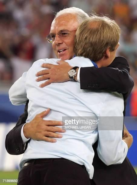 German head coach Juergen Klinsmann is embraced by German football legend and president of the World Cup organising committee Franz Beckenbauer...