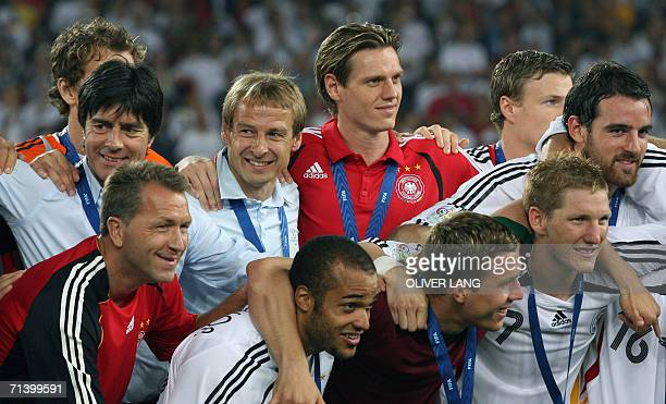 German head coach Juergen Klinsmann joins his team as they pose following the medal ceremony for the team's victory in the third-place playoff 2006...