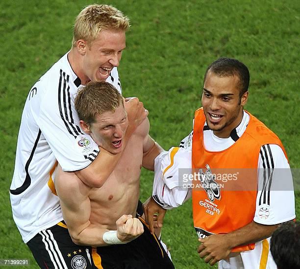 German midfielder Bastian Schweinsteiger celebrates scoring his second goal with German forward Mike Hanke and German midfielder David Odonkor during...