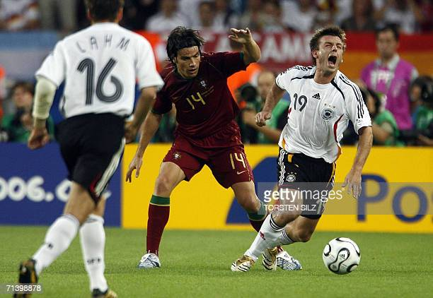 German midfielder Bernd Schneider shouts as he fights for the ball with Portuguese defender Nuno Valente while German defender Philipp Lahm looks 08...