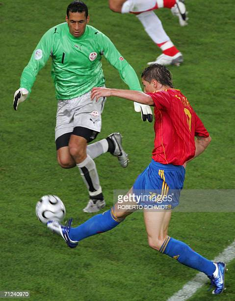 Spanish forward Fernando Torres shoots past Tunisian goalkeeper Ali Boumnijel to score the goahead goal during the opening round Group H World Cup...