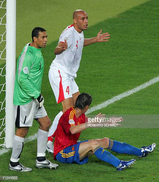 Tunisian defender Alaeddine Yahia gestures in vain after fouling Spanish forward Fernando Torres as Tunisian goalkeeper Ali Boumnijel looks on during...