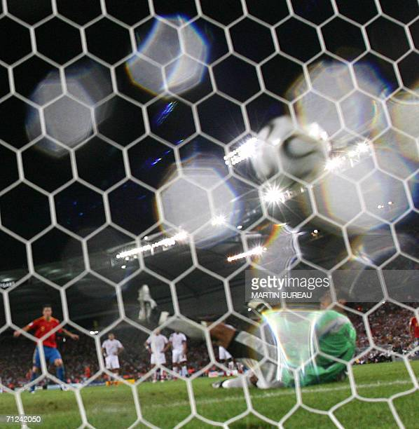Tunisian goalkeeper Ali Boumnijel fails to block a penalty kick by Spanish forward Fernando Torres in the rain in the opening round Group H World Cup...