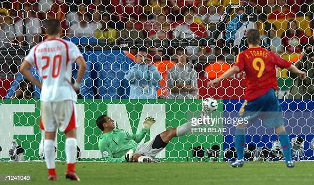 Tunisian goalkeeper Ali Boumnijel fails to stop a penalty kick by Spanish forward Fernando Torres as Tunisian midfielder Hamed Namouchi looks on...