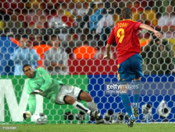 Tunisian goalkeeper Ali Boumnijel fails to stop a penalty kick by Spanish forward Fernando Torres during the opening round Group H World Cup football...