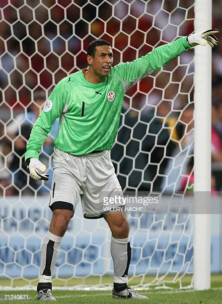 Tunisian goalkeeper Ali Boumnijel gestures to his players during the opening round Group H World Cup football match between Spain and Tunisia at...