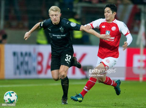 Stuttgart's Andreas Beck shields the ball against Mainz's Yoshinori Muto during the second half of a German DFBPokal thirdround match in Mainz on Dec...
