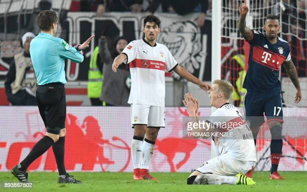 Stuttgart's defender Timo Baumgartl and defender Dennis Aogo react next to referee Patrick Ittrich during the German first division Bundesliga...