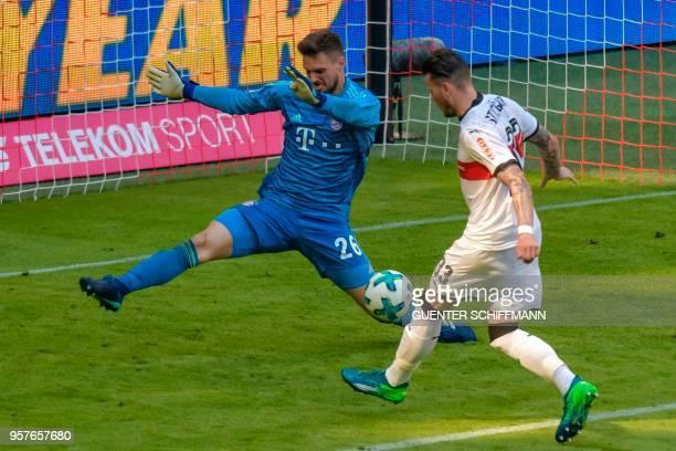 Stuttgart's German forward Daniel Ginczek shoots to score his team's fourth goal in front of Bayern Munich's German goalkeeper Sven Ulreich during...