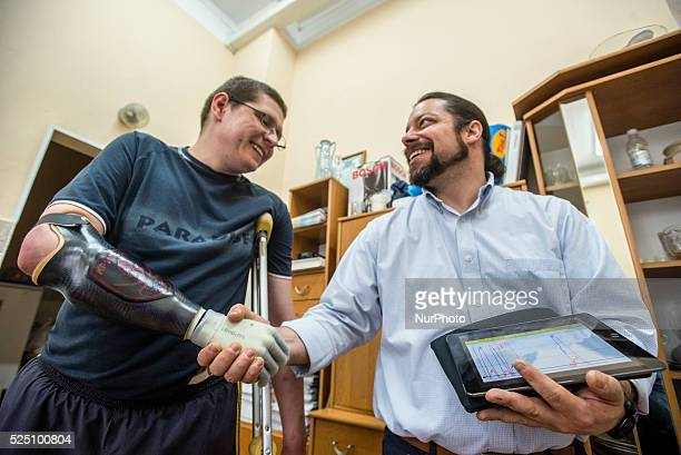 Stuzhenko Vasyl who lost his arm and a leg during fighting near Illovaisk in the Donetsk region last August shakes hand by his bionic hand to...