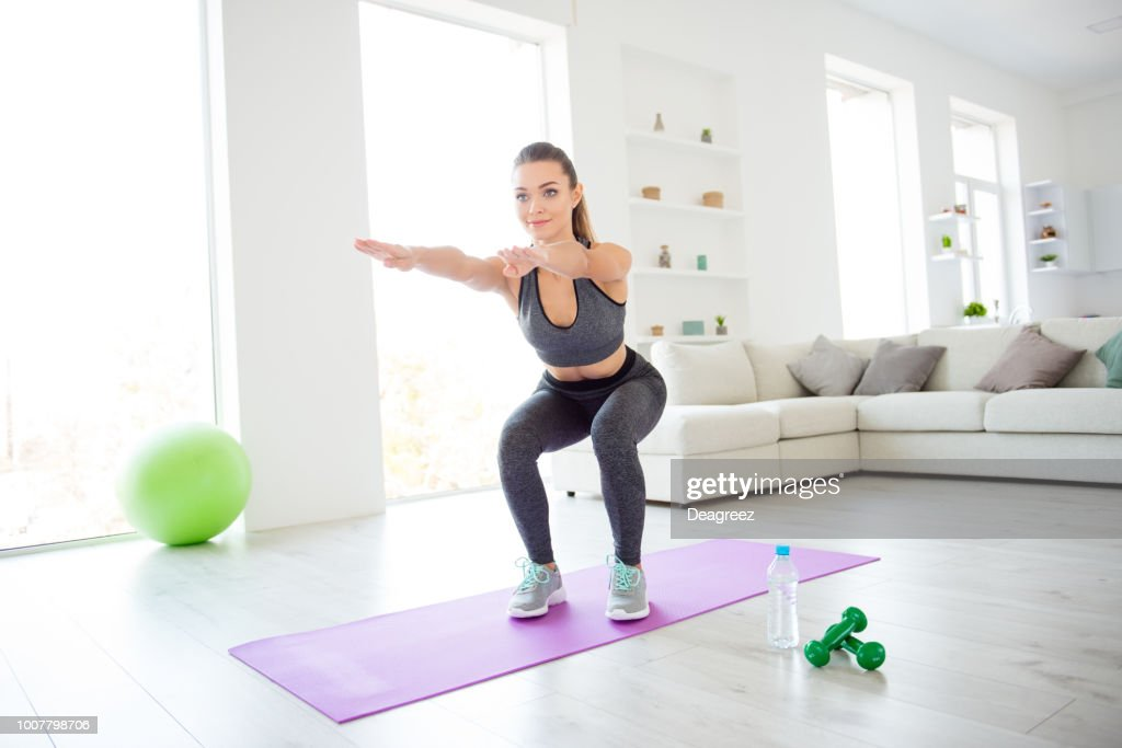 Style vitality beautiful figure healthy soul and body concept. Photo portrait of beautiful pretty charming lovely focused confident lady sportive shoes tight leggings doing squat against loft window : Stock Photo