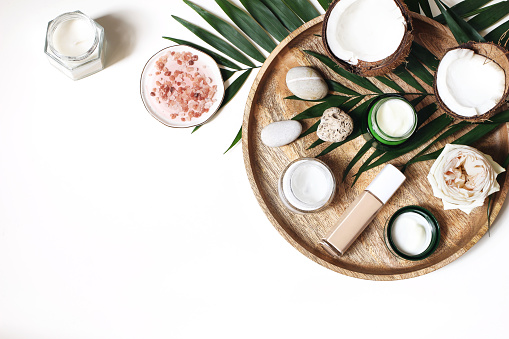 Styled beauty composition. Skin creams, makeup bottle, rose and pebble stones on wooden tray. Coconuts, tropical palm leaves decoration. Cosmetics, spa concept. Empty space, flat lay, top view. 1134972515