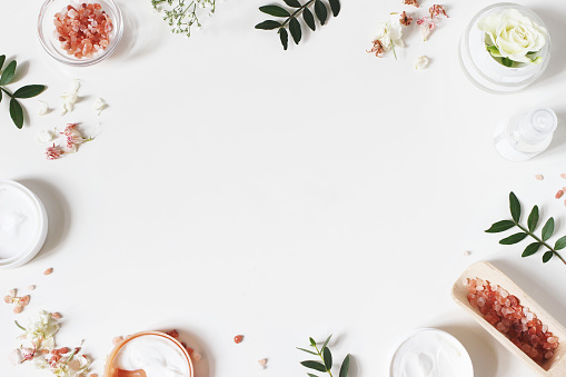 Styled beauty frame, web banner. Skin cream, tonicum bottle, dry flowers, leaves, rose and Himalayan salt. White table background. Organic cosmetics, spa concept. Empty space, flat lay, top view. 1125431744