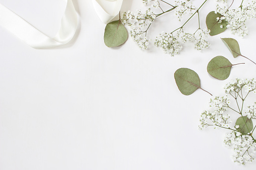 Styled stock photo. Feminine wedding desktop mockup with baby's breath Gypsophila flowers, dry green eucalyptus leaves, satin ribbon and white background. Empty space. Top view. Picture for blog 909314494