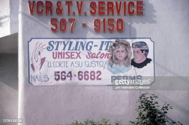 Styling-It Unisex Salon in South Gate, California has an image of a fashionable man and woman painted on the wall next the the company name, 1995.