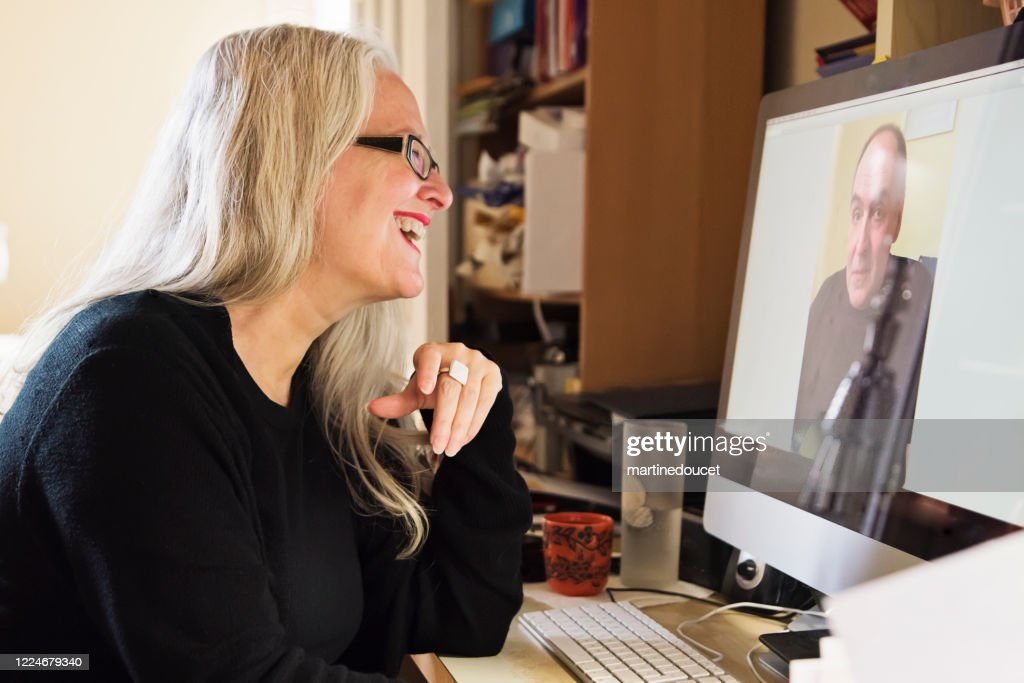 Stylish 50+ woman in video conference working from home. : Stock Photo