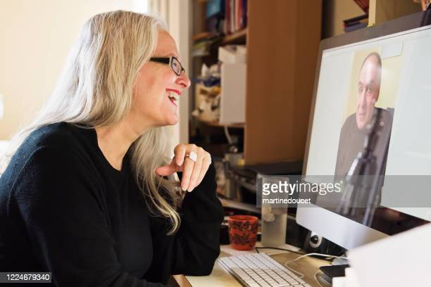 """stylish 50+ woman in video conference working from home. - """"martine doucet"""" or martinedoucet stock pictures, royalty-free photos & images"""