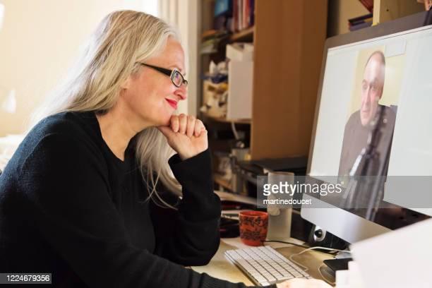 """stilvolle 50+ frau in video-konferenz arbeiten von zu hause aus. - """"martine doucet"""" or martinedoucet stock-fotos und bilder"""