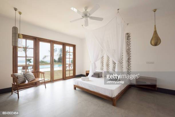stylish apartment bedroom with double bed - mosquito net stock photos and pictures