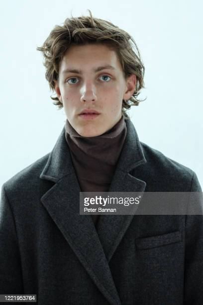 stylish, attractive young man wearing coat against white background - cheveux mi longs photos et images de collection