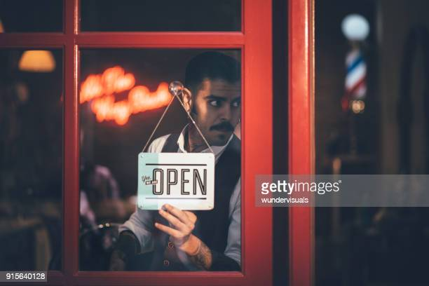Stylish barber opening barber shop with sign on business door