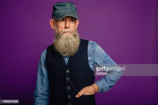 elegante uomo anziano barbuto - mani in tasca foto e immagini stock