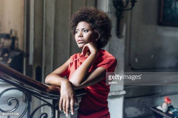 style belle jeune cubaine femme se penchant sur la balustrade à l'intérieur