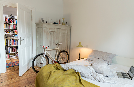 Stylish bedroom witch trendy single speed bike leaning at a cabinet and a laptop on bed. - gettyimageskorea