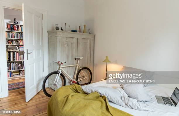 stylish bedroom witch trendy single speed bike leaning at a cabinet and a laptop on bed. - camera da letto foto e immagini stock