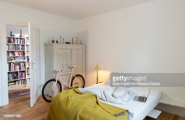 Stylish bedroom witch trendy single speed bike leaning at a cabinet and a laptop on bed.