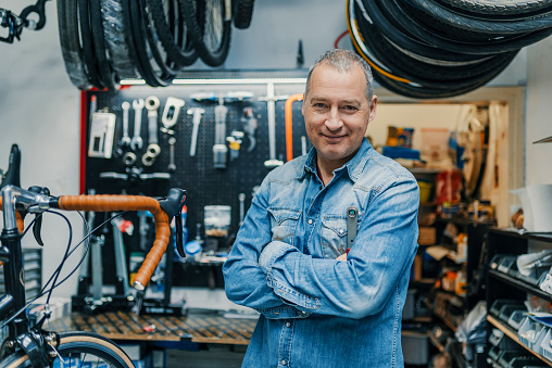 Stylish bicycle mechanic standing in his workshop 950671616