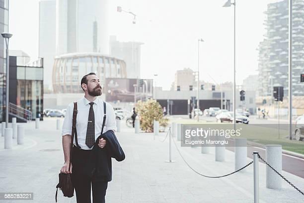 Stylish businessman carrying jacket walking in city