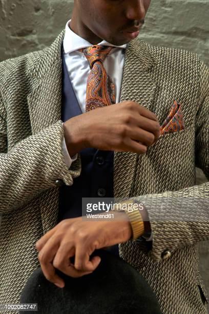 stylish businessman holding a beret and checking his pocket square - pochette bavero foto e immagini stock