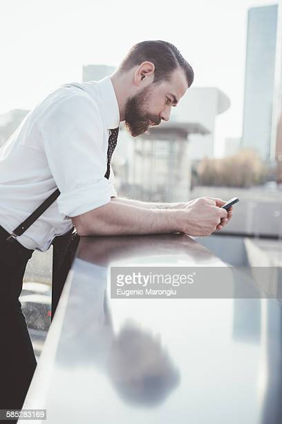 Stylish businessman reading smartphone text leaning against office balcony