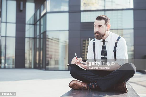 Stylish businessman sitting cross legged making diary notes from smartphone outside office