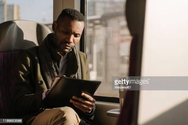 stylish businessman taking notes while traveling by train - bahnreisender stock-fotos und bilder