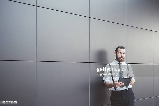 Stylish businessman using digital tablet and smartphone leaning against office wall