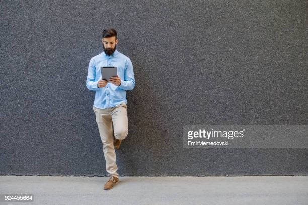 stylish businessman using digital tablet outdoors - emir memedovski stock pictures, royalty-free photos & images