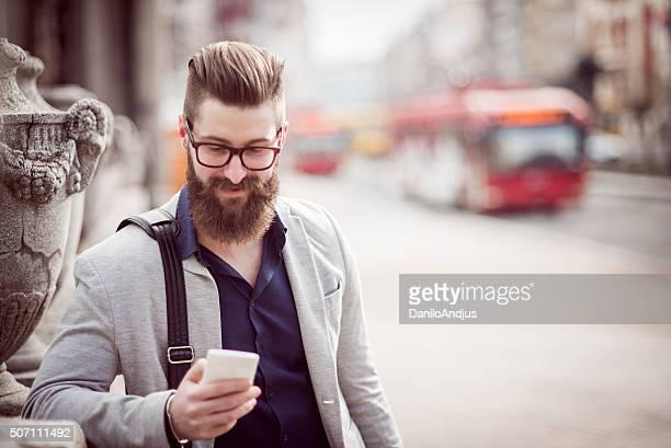 Elegante Uomo d'affari utilizzando il suo smartphone
