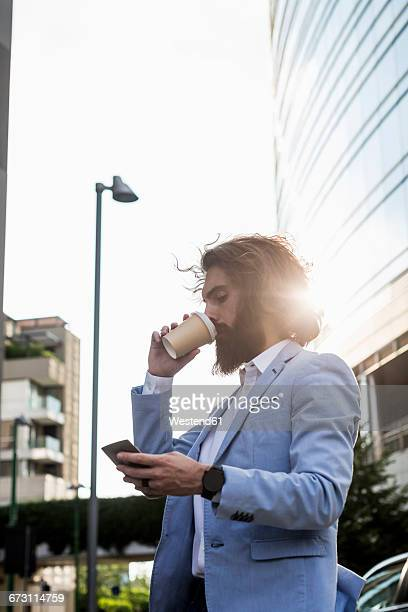 Stylish businessman with cell phone and coffee to go outdoors
