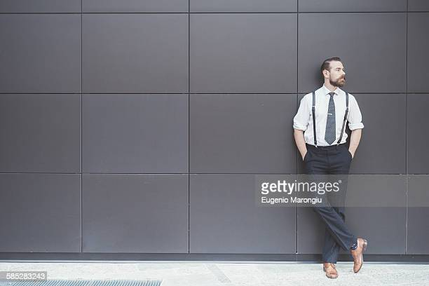 Stylish businessman with hands in pockets leaning against office wall