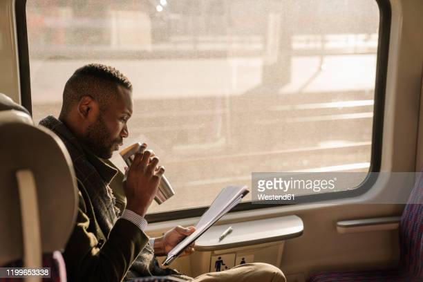 stylish businessman with reusable cup and documents in a train - convenience stock pictures, royalty-free photos & images